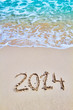 New 2014 year figures written on the sand