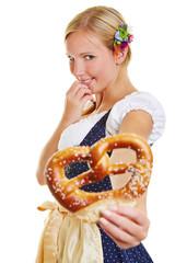 Woman in dirndl offering pretzel