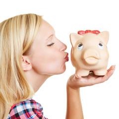Blond woman kissing piggy bank