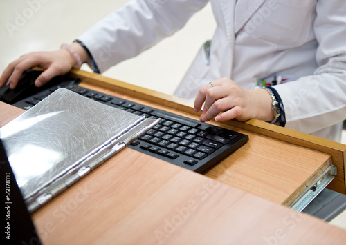 medical worker typing on computer.