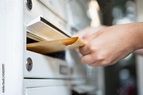 Leinwandbild Motiv Woman putting envelope in mailbox