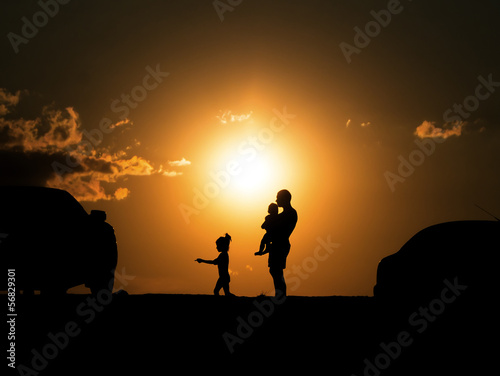 happy family of three people,celebrate outside at Sunset, Silhou