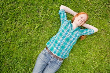 Carefree Woman Lying on a Green Field