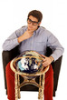 Young man pondering life with world globe in chair