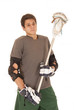 brunette young man in lacrosse pads holding stick