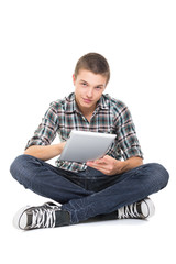 Cute teenage guy using tablet computer smiling