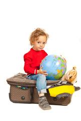 Toddler boy with globe sitting on luggage