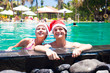 young couple in santa hats laughing in pool beach. new year