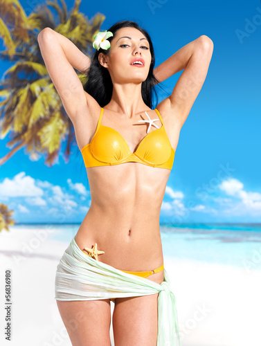 Woman with beautiful body in bikini at beach