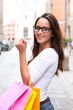 Happy young woman carring shopping bags in city street