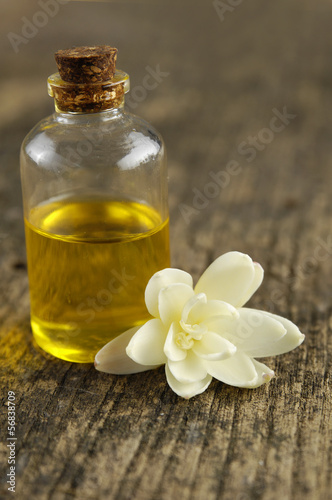 White Gardenia Blossom with spa oil in glass on driftwood