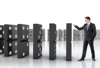 Businessman pushing dominoes