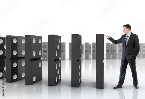 Businessman pushing dominoes