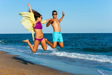 Crazy couple jump on beach.