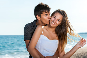 Happy teen couple embracing on beach.