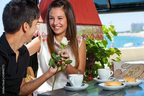 Teen boy giving flower to girlfriend in restaurant.