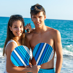 Teen couple with beach tennis rackets.