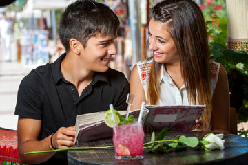 Young couple with restaurant menu at table.