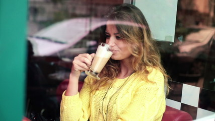 Beautiful woman drinking cafe latte in cafe