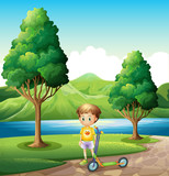 A young boy with a scooter standing near the river