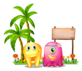 A yellow and a pink monster couple standing in front of the empt