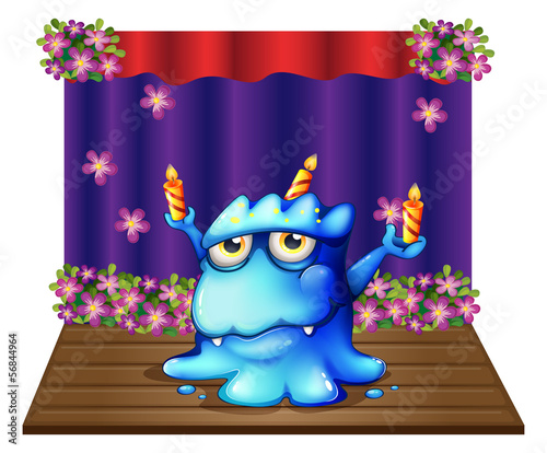 A stage with a blue monster balancing the three lighted candles