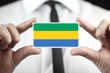 Businessman holding a business card with a Gabon Flag