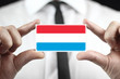 Businessman holding a business card with a Luxembourg Flag