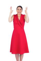 Surprised elegant brunette in red dress posing