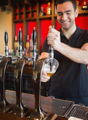 Handsome barkeeper pulling a pint of beer