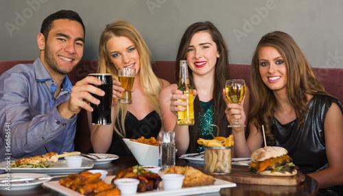 Friends having dinner together smiling at camera