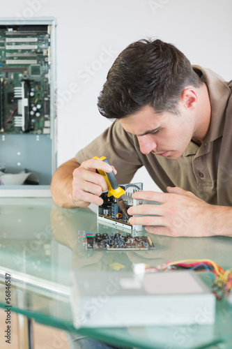 Handsome focused computer engineer repairing hardware with plier