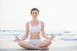 Peaceful slim brown haired model in white sportswear meditating