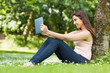 Smiling woman leaning against a tree in a park using her tablet