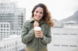 Cheerful gorgeous brunette in winter fashion holding disposable