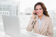 Happy businesswoman on the phone at her desk