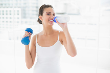 Cheerful natural brown haired woman in white sportswear drinking