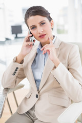 Thoughtful smart brown haired businesswoman making a phone call