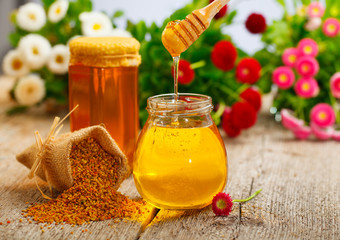 Honey in glass jars with flowers background