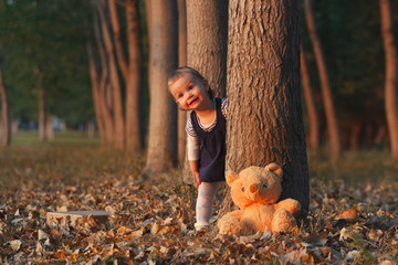 Cute little girl is playing hide and seek with her teddy bear