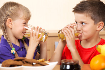 Two kids drink orrange juice while looking on each other