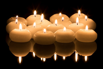 White candles on a black reflecting background
