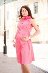 Beautiful pregnant woman in dress posing on street
