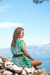 Young woman  sitting on cliff and looking to a sea
