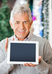 Happy Man Displaying Digital Tablet In Christmas Store