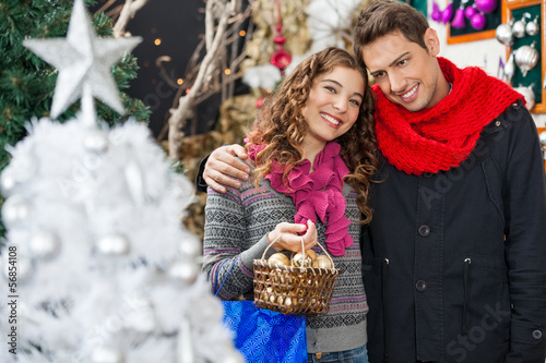 Woman Carrying Bauble Basket Standing With Man In Store