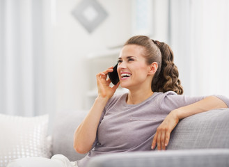 Happy young housewife talking cell phone in living room