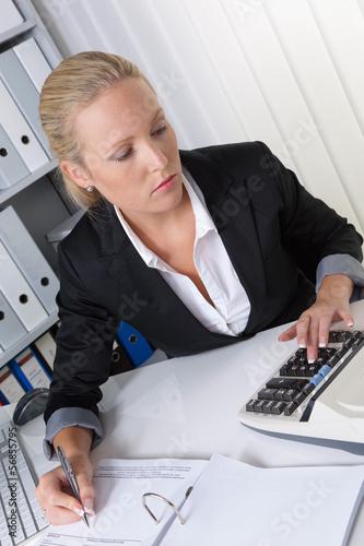 Frau mit Taschenrechner im Büro