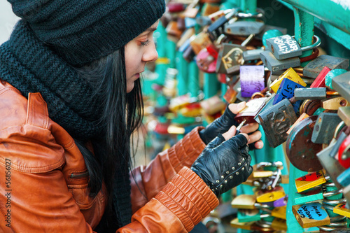 Girl opening a lock on a bridge