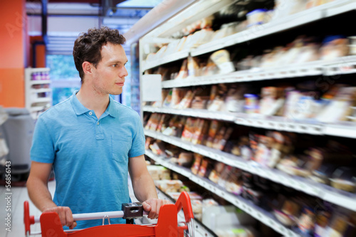 young attractive man choosing food in the supermarket